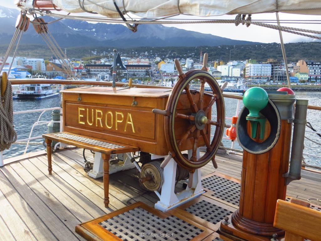 """Steuerrad der Bark Europa; im Hintergrund die """"Skyline"""" von Ushuaia"""